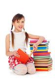 Smiley schoolgirl sitting near books — Stock Photo
