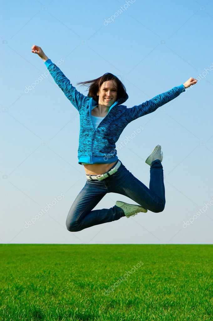 Cheerful woman jumping at the green field — Stock Photo #5160135