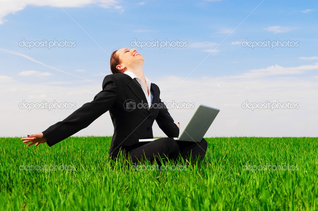 Happy woman with laptop sitting at the green field — Stock Photo #5160301