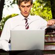 Businessman sitting in the park with laptop - Stock Photo
