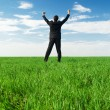 Glad businessman standing at the green grass — Stock Photo