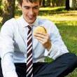 Young businessman with laptop eating hamburger — Stok fotoğraf