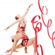 Stock Photo: Two flexible gymnasts dancing with red ribbons