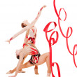 Two flexible gymnasts dancing with red ribbons — Stock Photo #5181033