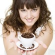Smiley young woman holding cup of coffee beans — Stock Photo