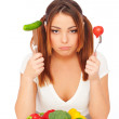 Woman sitting near plate with vegetables — Stock Photo #5182036