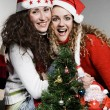 Happy friends with santa and christmas tree — Stock Photo