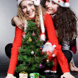 Smiley girls in red hats sitting near christmas tree — Stock Photo