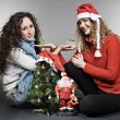 Two friends sitting near christmas tree — Stock Photo