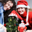 Women sitting near christmas tree — Stock Photo