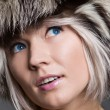 Attractive woman in fur hat looking up with interest — Stock Photo #5183370