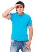 Handsome man in blue t-shirt is scrutinizing — Stock Photo