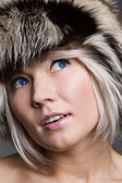Attractive woman in fur hat looking up with interest — Stock Photo
