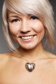 Smiley woman with silver heart — Stock Photo