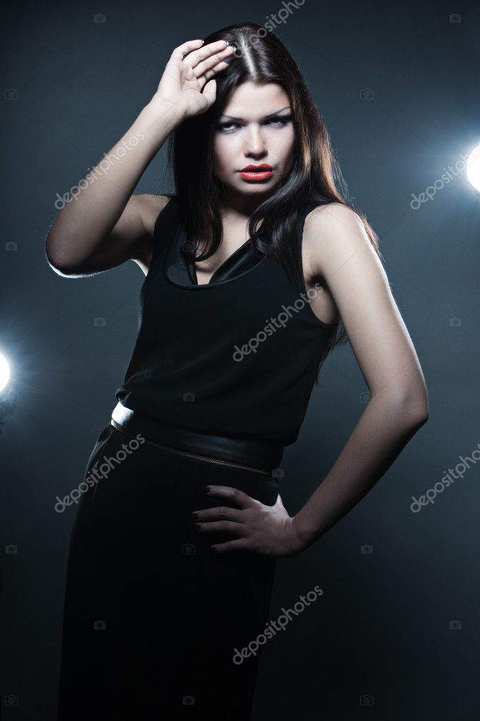 Fashion model in black dress posing against flashes — Stock Photo #5180780
