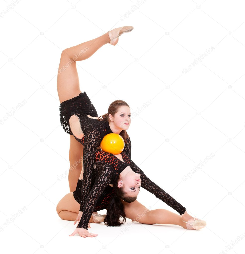 Two pretty gymnasts posing with yellow ball. isolated on white background — Stock Photo #5181023