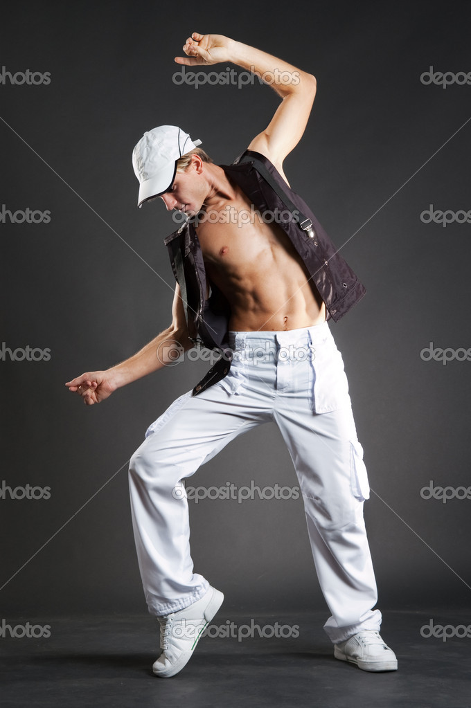 Attractive dancer in white cap posing against dark background — Stock Photo #5181662