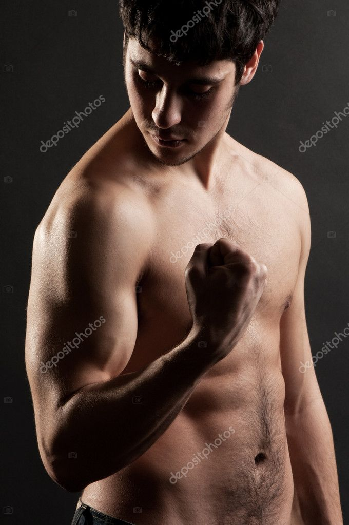 Sportsman looking at his biceps against dark background — Stock Photo #5182755