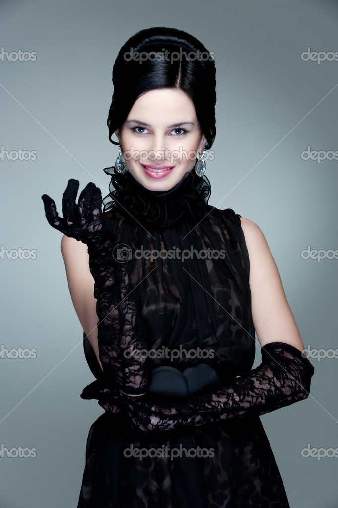 Attractive young woman in black dress posing against grey background — Stock Photo #5182901