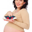Pregnant woman holding small sneakers — Stock Photo
