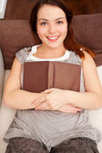 Smiley young woman with book — Stock Photo