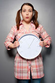 Young disturbed woman with wall clock — Stock Photo