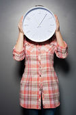 Woman holding wall clock infront of her face — Stock Photo