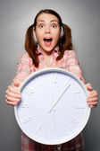 Young disturbed woman holding wall clock — Stock Photo