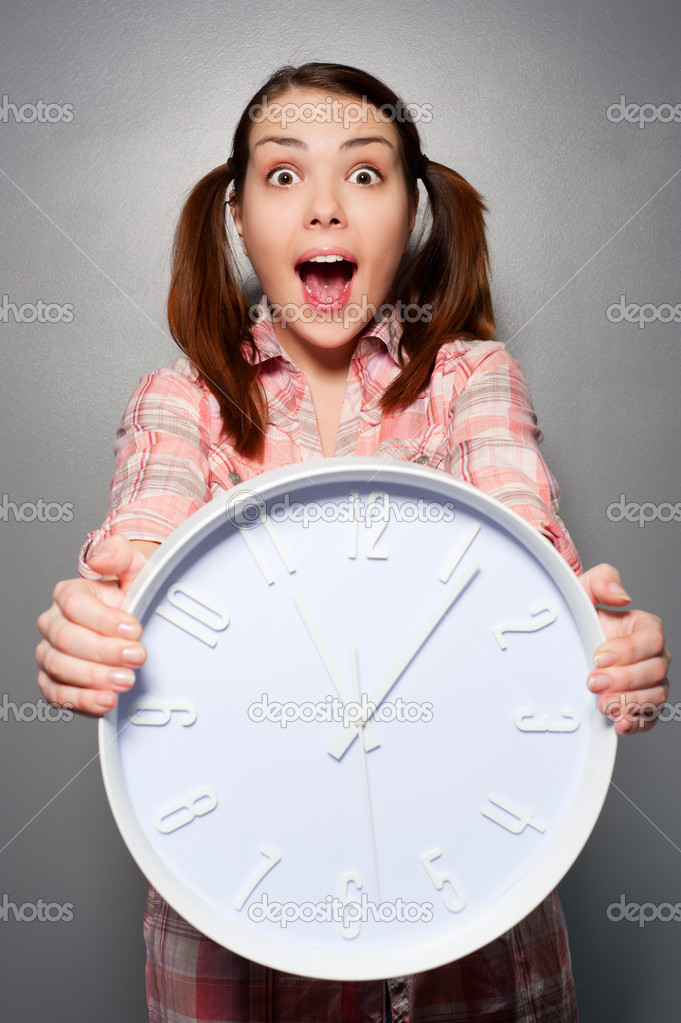 Portrait of young disturbed woman holding wall clock  — Stock Photo #5329852