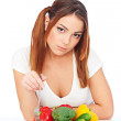 Woman sitting near plate with vegetables — Stock Photo