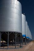 A row of shiny, steel grain silos in a field — Stock Photo