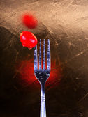 Fork and tomatoe — Stock Photo