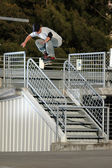 Skateboarder jumping over a handrail — Stock Photo
