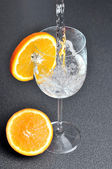 Pouring water into glass with orange slice — Stock Photo