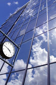 Clock on blue office building background — Stock Photo
