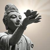 Buddhist statue providing offerings — Stock Photo