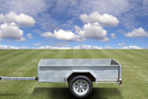 Empty trailer on green grass — Stock Photo