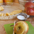 Peeled apple with pie ingredients in the background — Stock Photo