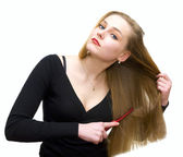 Young girl combs hair — Stock Photo