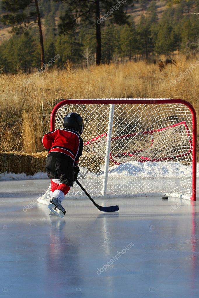 Child hockey player playing outdoor pond hockey — Stock Photo #5042663