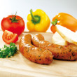 Two sausages and vegetable on wooden board — Stock Photo #4984236