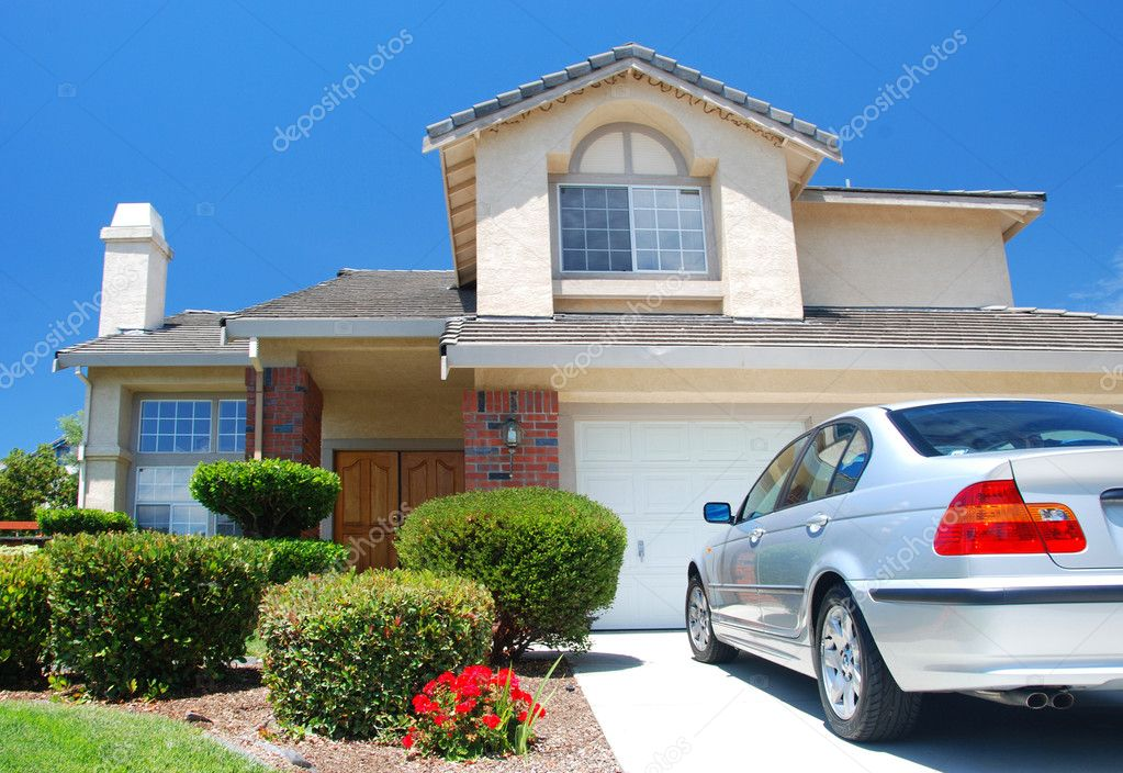 New American dream home with a beautiful blue sky in background and brand new car parked outside — Stock Photo #4985723