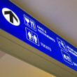 Royalty-Free Stock Photo: Detailed view of blue airport sign showing directions.