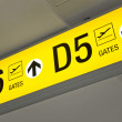 Detailed view of yellow airport departure sign showing direction to gates - Stock Photo