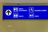 Detailed view of blue airport sign showing directions. — Stock Photo