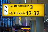 Detailed view of yellow airport departure sign showing direction to gates — Stock Photo
