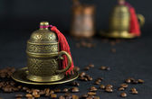 Scattered coffee against an ancient Turkish cup for coffee — Stock Photo