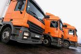 Three orange trucks — Stock Photo