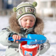 Kid collects snow — Stock Photo