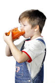 The boy drinking carrot juice — Stock Photo